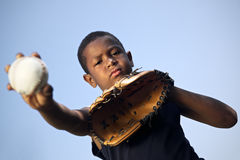 Sport, baseball and kids, portrait of child throwing ball. Sport, baseball and kids, portrait of child with glove holding ball and looking at camera Stock Photography