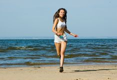 Sport on the beach. Young woman running alone on the beach Stock Photos