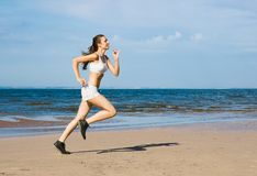 Sport on the beach. Young woman running alone on the beach Stock Image