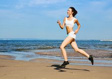 Sport on the beach. Young woman running alone on the beach Stock Photo