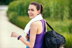 Sport. Beautiful smiling happy young woman before or after workout and running look from back on nature background. With purple t-shirt and white towel royalty free stock image
