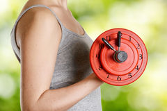 Beginner female athlete holding dumbbell with cloc Stock Image