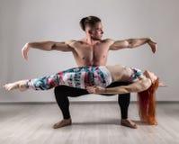 Sport bemannt und die Frau, die acroyoga Übungen in einem grauen Hintergrund tut Lizenzfreies Stockfoto