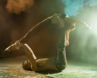 Sport bemannt und die Frau, die acroyoga Übungen in einer Dunkelkammer mit buntem Rauche tut Lizenzfreie Stockfotos
