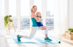 Sport bemuttert teilnimmt an Eignung und Yoga mit Baby zu Hause Lizenzfreie Stockfotografie