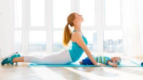 Sport bemuttert teilnimmt an Eignung und Yoga mit Baby zu Hause Stockfotos