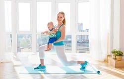 Sport bemuttert teilnimmt an Eignung und Yoga mit Baby zu Hause Lizenzfreie Stockfotos