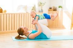 Sport bemuttert teilnimmt an Eignung und Yoga mit Baby zu Hause Lizenzfreie Stockbilder