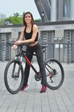 Sport Berijdt het schoonheids geschikte meisje een fiets op een open weg aan de zonsondergang stock foto