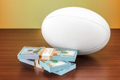 Sport bets. Rugby ball with dollar packs on the wooden table, 3D Stock Photography