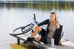 Sport biking young woman sitting by lake Stock Photography