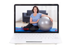 Sport blog concept - mature woman showing her training online on. Sport blog concept - sporty mature woman showing her training online on laptop screen Royalty Free Stock Photography
