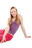 Sport blonde girl. Young beautiful blonde girl in sport wear sitting on the floor royalty free stock photo