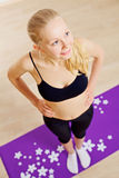 Sport blonde woman standing on mat Stock Image