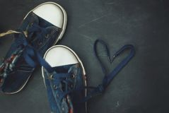 Sport blue Jeans Boots Children Heart Shape Laces over Textured Grounge Chalckboard. Toned. Education and Parenting. Sport blue Jeans Boots Children Heart Shape royalty free stock photography