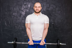 Sport, bodybuilding, lifestyle and people concept - smiling man with barbell Stock Images