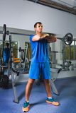 Sport, bodybuilding, lifestyle and people concept - young man with barbell doing squats in gym Stock Photo