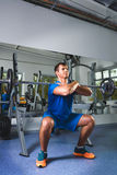 Sport, bodybuilding, lifestyle and people concept - young man with barbell doing squats in gym Royalty Free Stock Photo