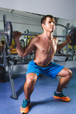Sport, bodybuilding, lifestyle and people concept - young man with barbell doing squats in gym Royalty Free Stock Image