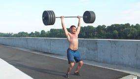 Sport, bodybuilding, livsstil och folkbegrepp - ung man med hanteln som böjer muskler i idrottshall arkivfilmer