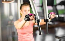 Sport bodybuilding som utbildar - kvinna i idrottshallen arkivbild