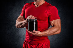 Sport, bodybuilding, strength and people concept - young man sta. Beautiful young athletic man holding a jar of sports nutrition Royalty Free Stock Photo