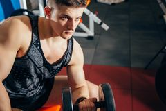 Sport, bodybuilding, training and people concept - close up of young man with dumbbell flexing muscles in the gym. royalty free stock photography