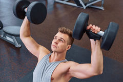 Sport, bodybuilding, training and people concept - young man with dumbbell flexing muscles. men working with dumbbells his body at. Sport, bodybuilding, training Stock Images