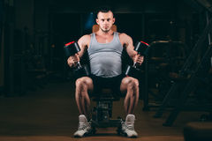 Sport, bodybuilding, weightlifting, lifestyle and people concept - young man with dumbbells flexing muscles in gym Royalty Free Stock Photos