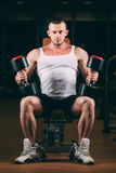 Sport, bodybuilding, weightlifting, lifestyle and people concept - young man with dumbbells flexing muscles in gym Royalty Free Stock Image