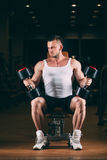 Sport, bodybuilding, weightlifting, lifestyle and people concept - young man with dumbbells flexing muscles in gym Stock Images