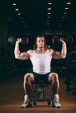 Sport, bodybuilding, weightlifting, lifestyle and people concept - young man with dumbbells flexing muscles in gym Stock Photography