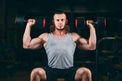 Sport, bodybuilding, weightlifting, lifestyle and people concept - young man with dumbbells flexing muscles in gym Royalty Free Stock Photo