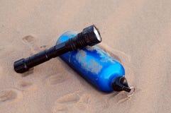 Sport bottle and flashlight in desert. A blue sport bottle and flashlight in desert Stock Photos