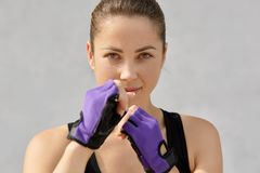 Sport, boxing and people concept. Sweat self determined fit young woman wears special gloves, goes in for boxing, keeps hands in f royalty free stock images