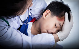 Sport boy's temple with a bruise. Youth asian (thai) sport boy in blue uniform. Child temple with a bruise, doctor perform first aid by checking. Shoot in studio Stock Image