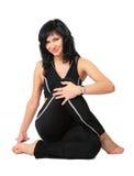 Sport brunette in black  makes exercise Royalty Free Stock Photos