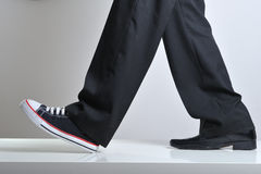 Sport and business. Walking legs with business shoe in a foot and sneaker on other Royalty Free Stock Image