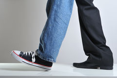Sport and business. Mans legs wearing jeans and sneakeron on a leg and suit on other Stock Image