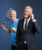 Sport and business look. Portrait of senior sporty man and old businessman holding in hands a mobile phone while standing at  bacground Stock Photography