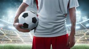 sport Calciatore professionista che tiene pallone da calcio sui precedenti dello stadio Fine in su immagini stock libere da diritti