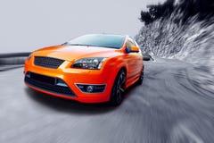 Sport car. Beautiful orange sport car on road Royalty Free Stock Image