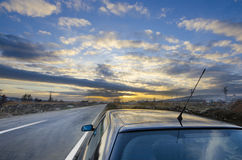 Sport car drive road to sunset horizon. Sport car parked on road side in sunset colorful weather Royalty Free Stock Photo