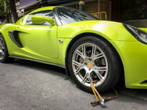 Sport car has been wheel-cramped because of illegal parking. Traffic law enforcement royalty free stock photo