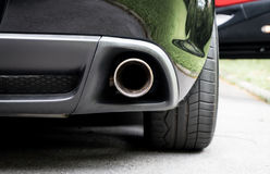 Sport Car muffler in the back of a black luxury sport car. Sport Car muffler in the back of a luxury sport car stock photography