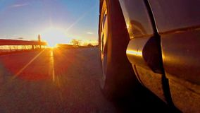 Sport car race with sunset rays shining on tire. Beautiful low angle view of sport car race with sunset rays shining on tire, TIMELAPSE