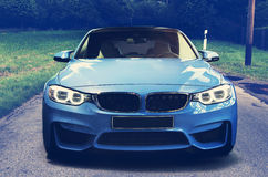 Sport car on the road. New luxury blue car on empty country road in a dark day Royalty Free Stock Photo