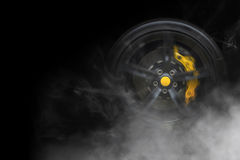 Sport car wheel with with yellow breaks and lot of smoke tire. Isolated generic sport car wheel with yellow breaks drifting and smoking on a black background Royalty Free Stock Image