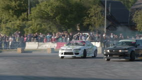 Sport cars competing in drifting championship. NOVOSIBIRSK, RUSSIA - JUNE 03, 2016: Slow motion of two sport cars competing on race track during drift stock video footage