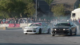 Sport cars competing in drifting. NOVOSIBIRSK, RUSSIA - JUNE 03, 2016: Drifting championship. Two sport cars competing on race track stock video